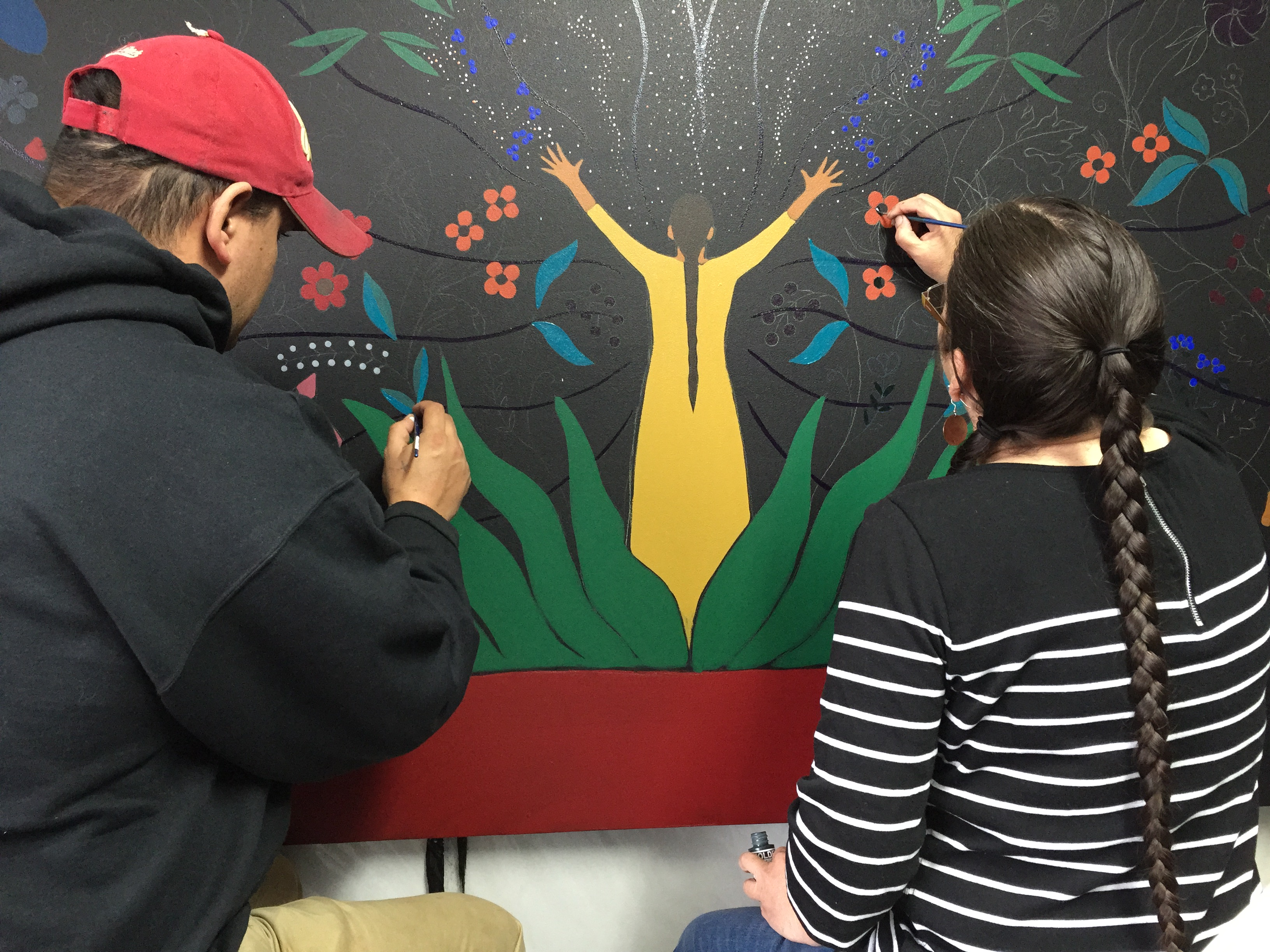 "Isaac & Christi working on ""Odemin Qwe"": a piece about strawberry teachings."